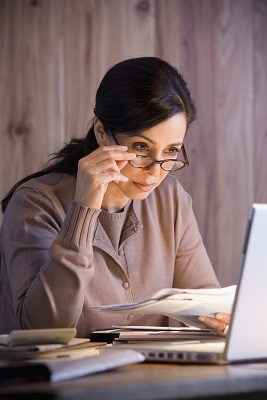 Woman with glasses studying at laptop